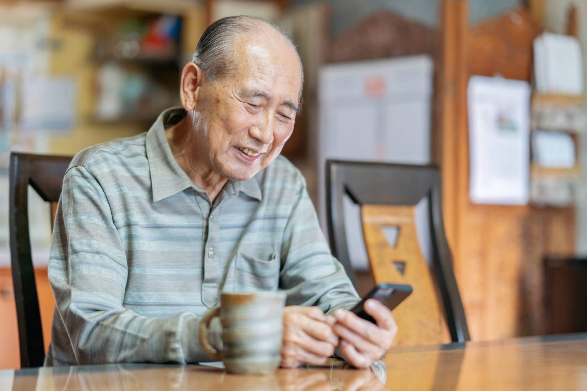 Portrait of senior man while using smart phone