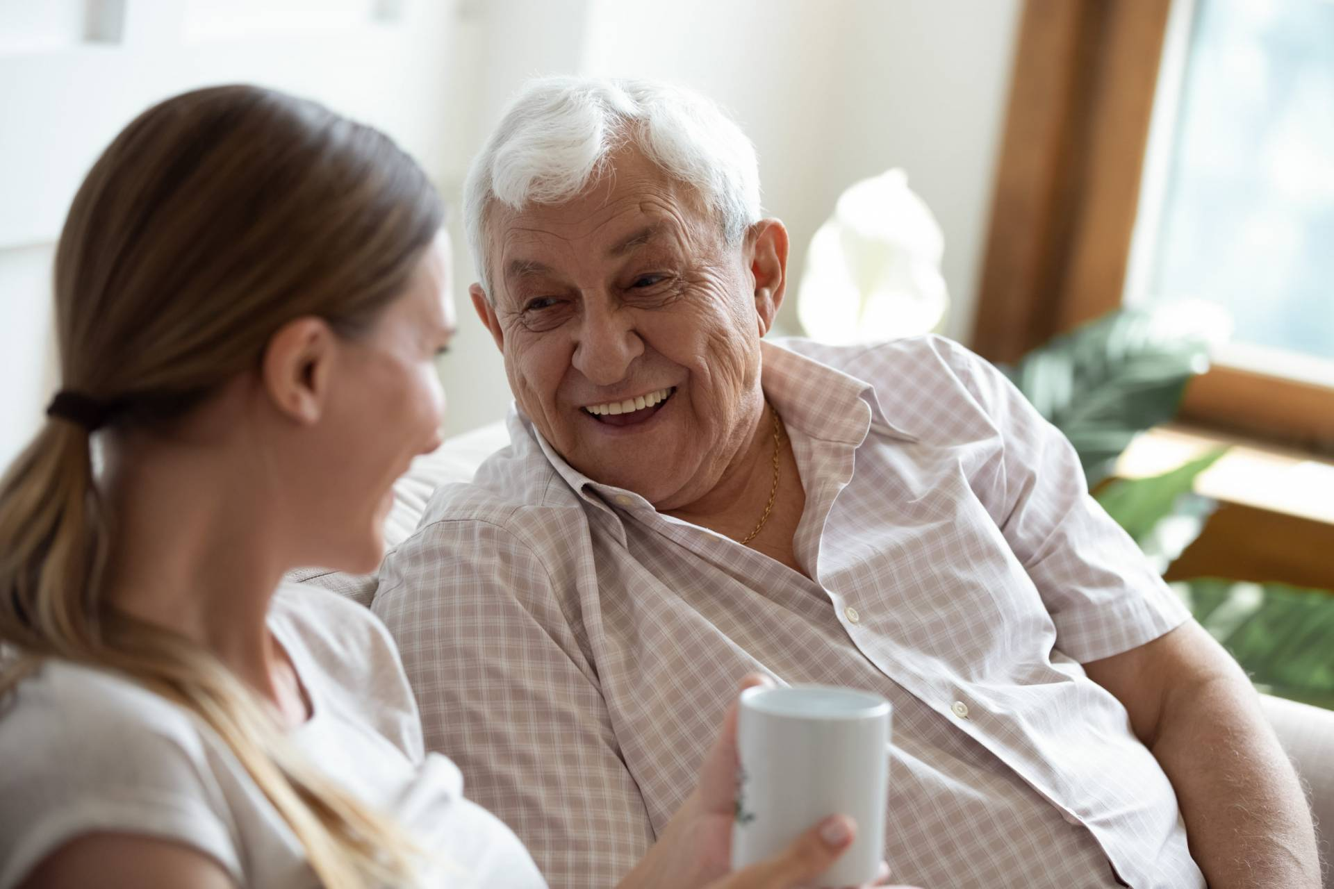 Happy old man talking with smiling grown up adult daughter.