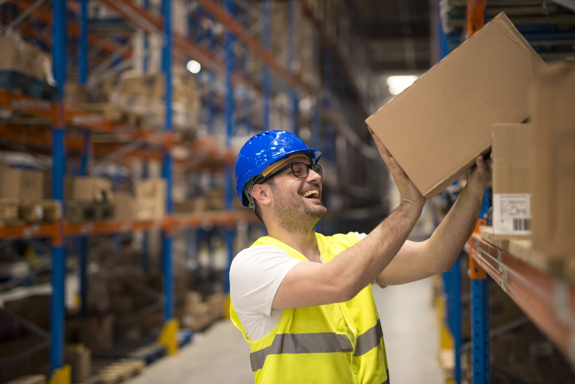 Working at warehouse. Smiling warehouse worker moving boxes on the shelf.