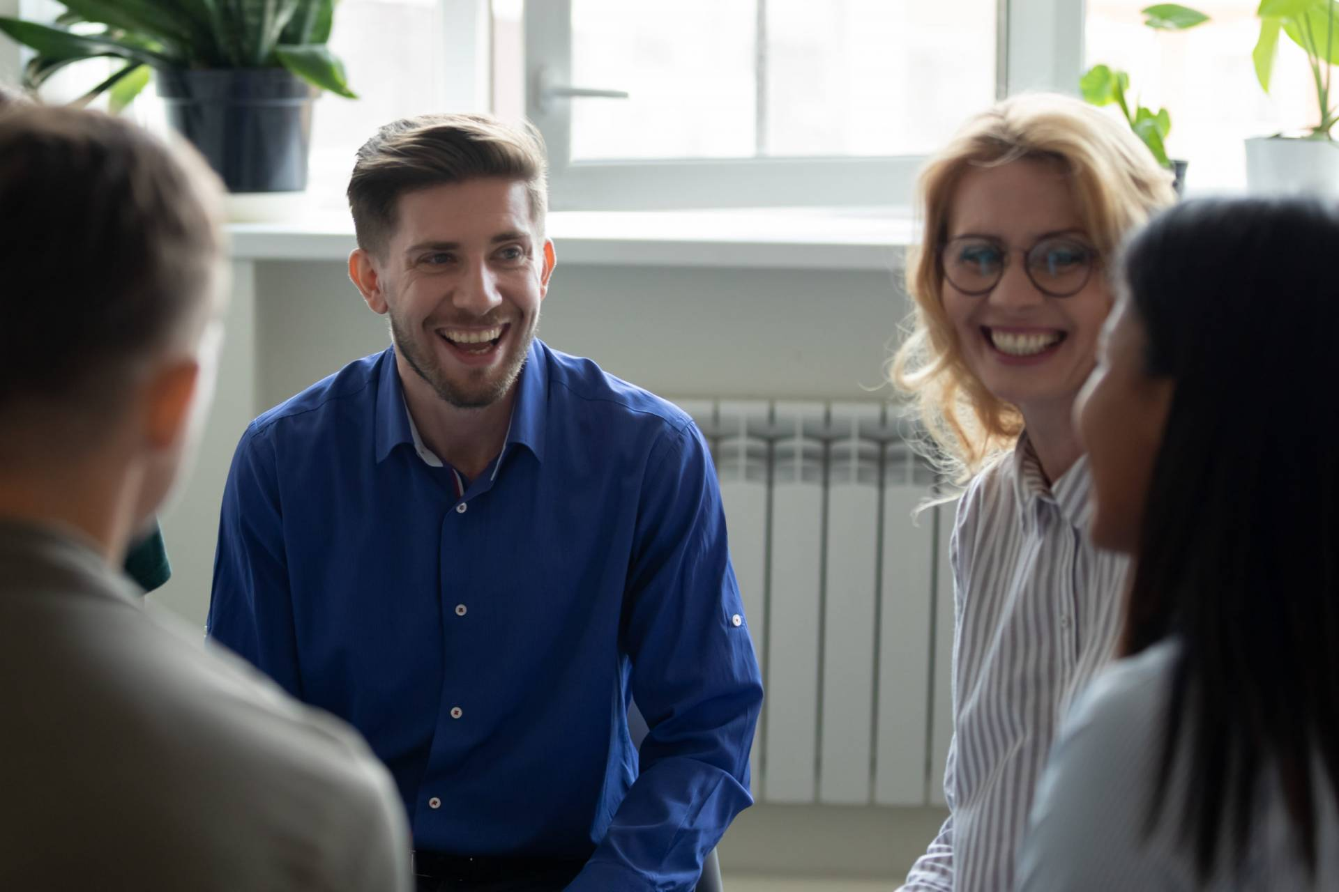 Overjoyed diverse people have fun engaged in team therapy indoors